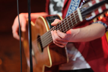Six string acoustic giant guitar in the hands of a musician