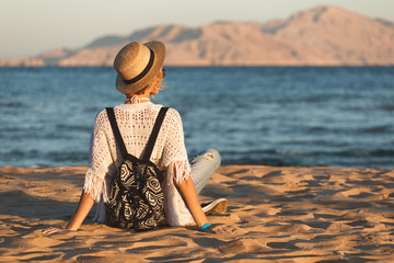 Beach woman happy in hat having summer fun during travel holidays vacation. Girl sits on the sand and looks at the water, the view from the back