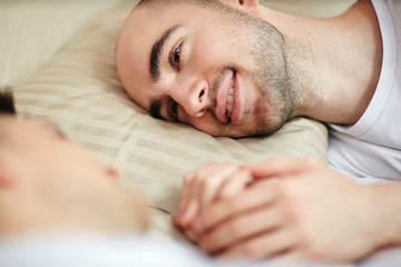 Young smiling man with his head on pillow looking at his partner in bed