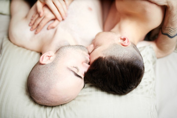 Young amorous homosexual men sleeping together on one pillow