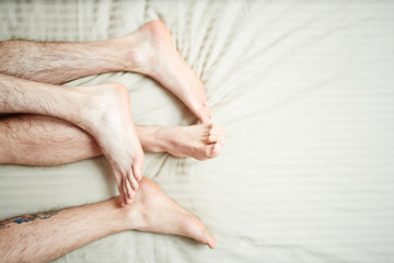Feet and hairy legs of homosexual couple during sleep in bed