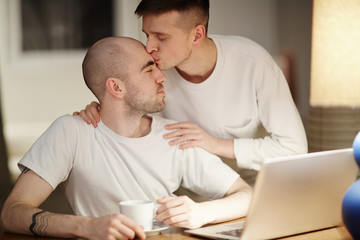 Amorous gay man kissing his lover while spending leisure at home