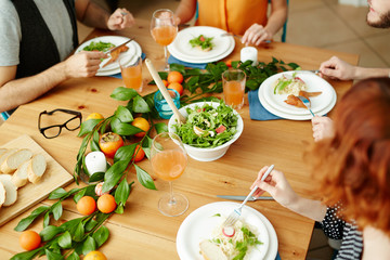 View of wooden table with festive food: vegetarian salad, pasta with vegs, wheat bread and fruits