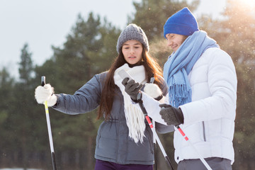 Young man showing his girlfriend message in smartphone while skiing on sunny winter day