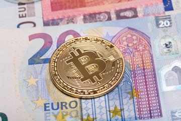 Golden bitcoin coin on euro banknotes close up
