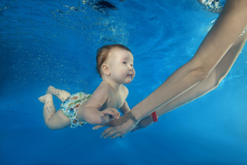 Mom teaches a boy to swim underwater in the pool