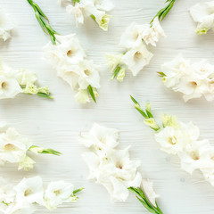 Flowers texture made of white gladioluses on wooden white background. Floral pattern of gladioli holiday greeting card. Flat lay, top view. Flowers texture