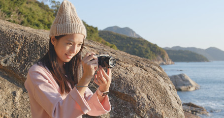 Woman taking photo by camera in the countryside