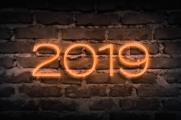Upcoming 2019 year as neon sign on brickwall pattern as backgound