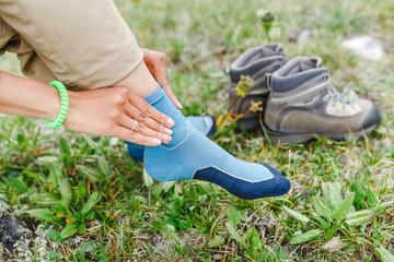 woman puts on high-tech trekking socks for hikes
