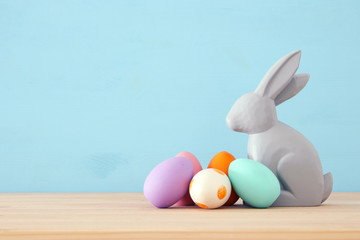 Cute bunny next to easter colorful eggs over colorful background.