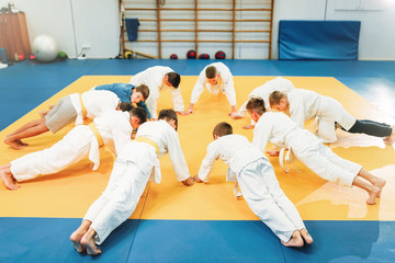 Boys in kimono makes push up exercise, kid judo