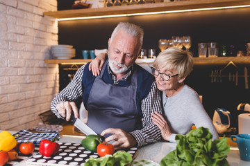 Senior couple preparing lunch together in kitchen.