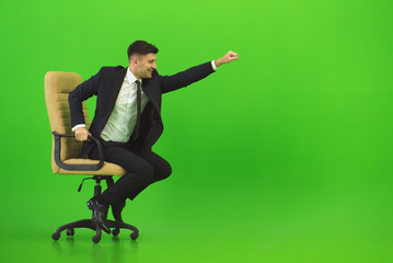The businessman fun on the chair on the green background