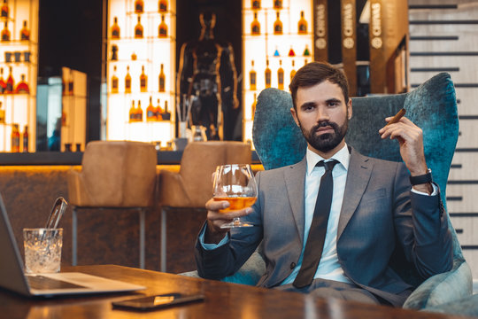Businessman sitting in a business center bar smoking cigar and drinking whiskey