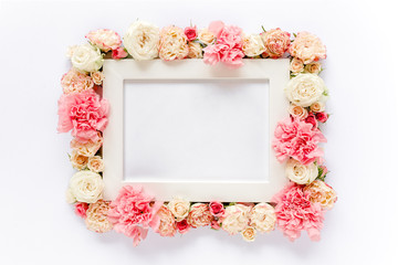 White frame decorated with pink roses flowers. Flat lay, top view. Floral background. Floral frame. Frame of flowers.
