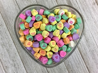 Valentine's Day candy hearts in a heart shaped glass dish on a distressed wood surface
