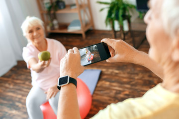 Senior couple exercise together at home taking pictures with apple