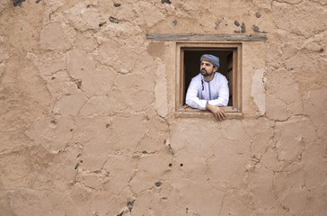 arab man in traditional omani outfit in an old castle, looking out of a window