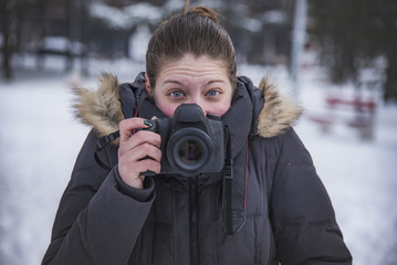 Funny young woman holding a professional dslr camera on a cold winter's day