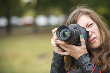 Young professional or amateur photographer taking a picture with her dslr camera