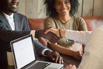 Happy young african american couple making deal handshaking caucasian insurance broker in cafe, black satisfied customer and realtor or sales person shaking hands at meeting in office with laptop
