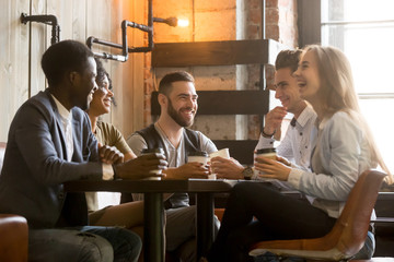 Multiracial friends having fun and laughing drinking coffee in coffeehouse, diverse young people talking joking sitting together at cafe table, multi ethnic millennials spending time in coffee shop Wall mural