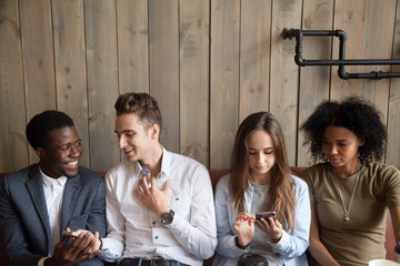 Millennial multiracial friends using phones talking at meeting, diverse young people spending time together with smartphones in cafe, serious and happy multiethnic mobile addicts obsessed with cells