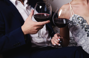 Caucasian male and female hands toasting wine glasses.