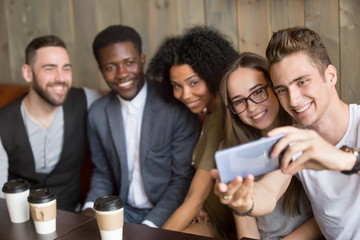 Young caucasian man making selfie on smartphone at meeting with multiracial millennial friends, diverse happy people having fun in cafe together taking group self-portrait photo on mobile phone