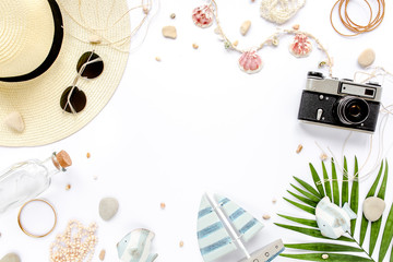 Traveler accessories, tropical palm leaf branches, camera on white background with empty space for text. Travel vacation concept. Summer background. Road frame set. Flat lay, top view.
