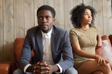 Frustrated upset african couple in quarrel sitting on sofa not talking after fight, stubborn disappointed black man ignoring sad depressed offended woman, problem in marriage relationships concept