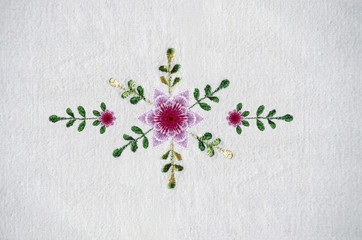 Embroidered satin stitch pattern with pink cloves and leaves