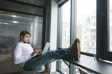A man put his feet on the table while working on a laptop. Boss put his feet on the table while working on a computer. Freelancer works in coworking.