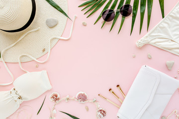 Feminine white swimsuit beach accessories on pink background with empty space for text. Travel vacation concept. Summer background. Road frame set. Traveler accessories. Flat lay, top view.