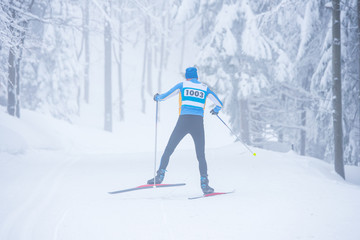 Professional nordic ski athlete in white winter nature. Sport photo, white edit space