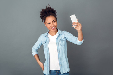 Young african woman isolated on grey wall studio casual daily lifestyle selfie photo