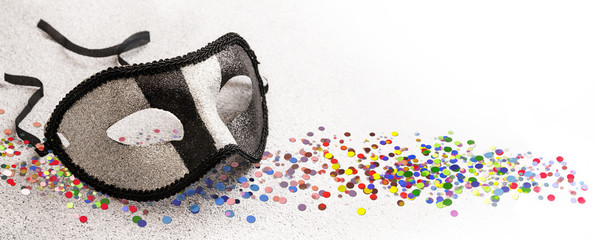 carnival mask in glittering silver and black and colorful confetti on a light gray  background with copy space, panoramic banner format