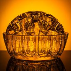 Decorative semicircular glass vase on a background of orange gradient