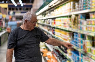 Senior man selecting some products in the supermarket
