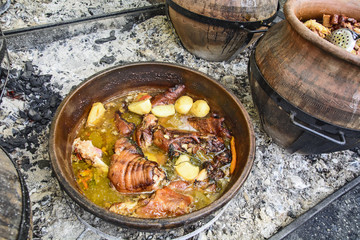 Cooking pork in a traditional earthen pot