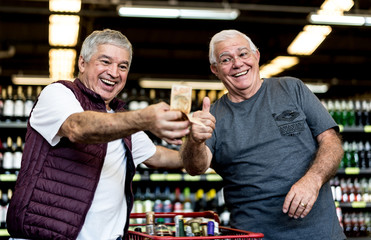 Senior friends happy with money in the supermarket