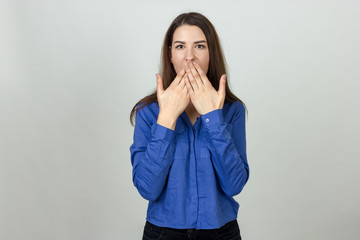Portrait of a pretty woman covering her mouth over gray background