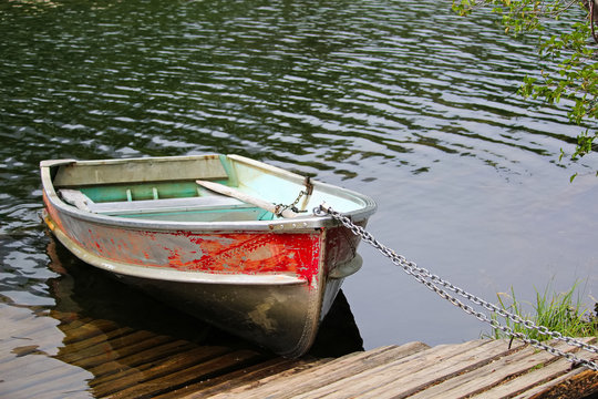 An aluminum row boat chained to the shore by a dock