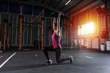 Athletic girl works out at the gym with a barbell disk