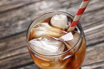Glass of refreshing cola with ice on wooden background, closeup