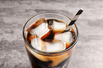 Glass of refreshing cola with ice on table, closeup