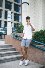 Young handsome Afro American man standing in front of huge modern business building