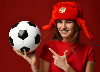 Russian style fan sport woman player in red uniform and ear-flap hat hold soccer ball celebrating happy smiling