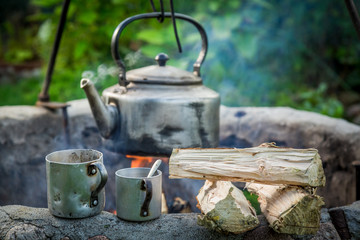 Freshly made coffee with kettle on campfire